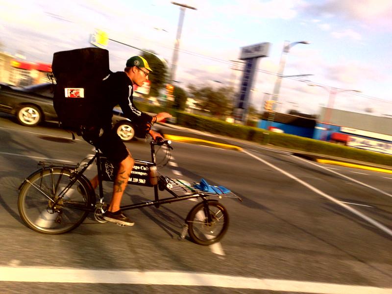 Fahrrad-Bote auf einem Cargobike an einetr Kreuzung mitten in der Fahrt uafgenommen
