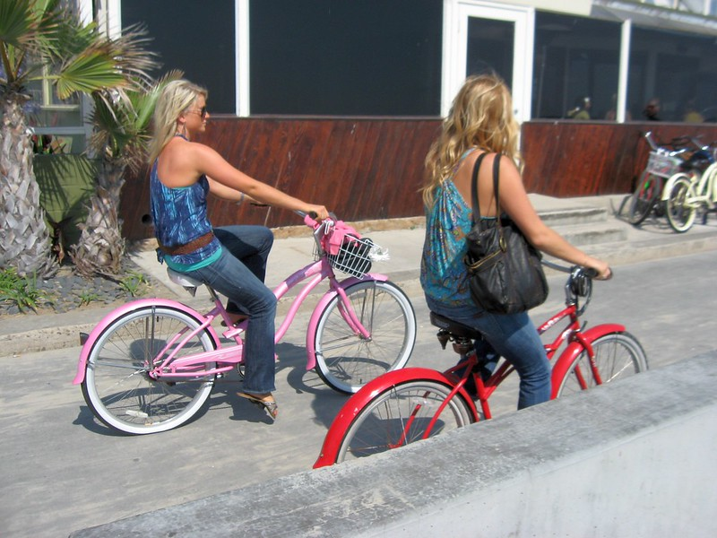 Zwai Frauen fahren bunte Cruiser an einer STrand-Promenade. Sie sind beie blond und die Cruiser rosa und rot.