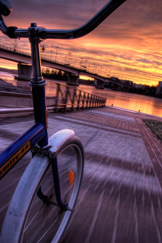 Starty - Rad fährt an einer Brücke abends aufs Flussufer zu