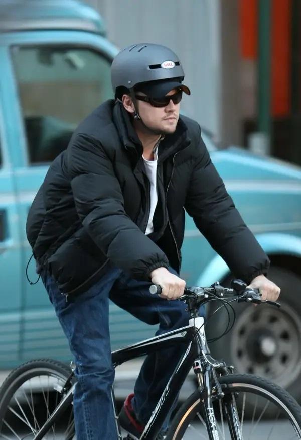 Leonardo DiCaprio auf einem Trekkingbike mit Schirmmütze und Bell Helm darüber