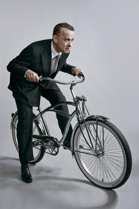 Tom Hanks auf einem Beachcruiser in silber. Er trägt Anzug und Krawatte.