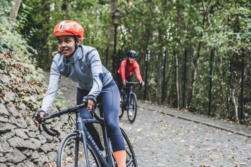 """Zwei junge Frauen beim gemeinsamen Fahrrad fahren - die eine vorne """"mit Migrationshintergrund"""" lächelt."""