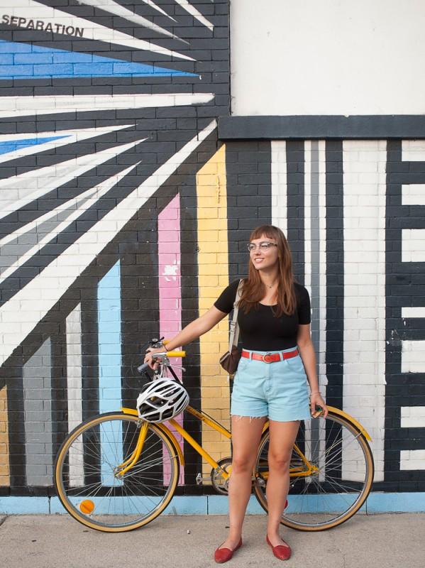 Eine schöne Frau namens April fährt ein gelbes Rad in Chicago und trägt dabei einen roten Gürtel und abgeschnittene Jeansshorts