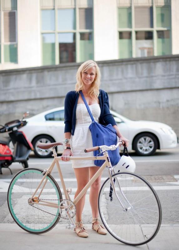 Eine schöne Frau namens Boo fährt ein cremefarbenes Rad in Chicago und trägt dabei ein weißes Minikleid und eine blaue Umhängetasche