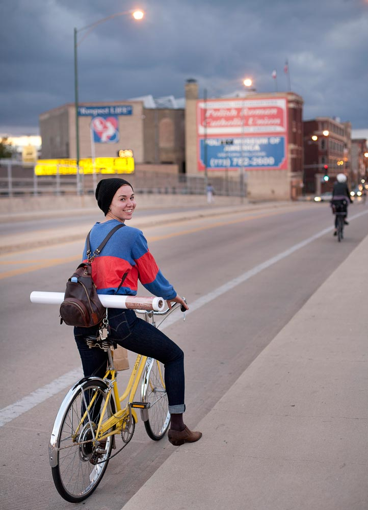 Eine schöne Frau namens Laura fährt ein gelbes Rad in Chicago und trägt dabei eine schwarze Mütze und braune Stiefeletten