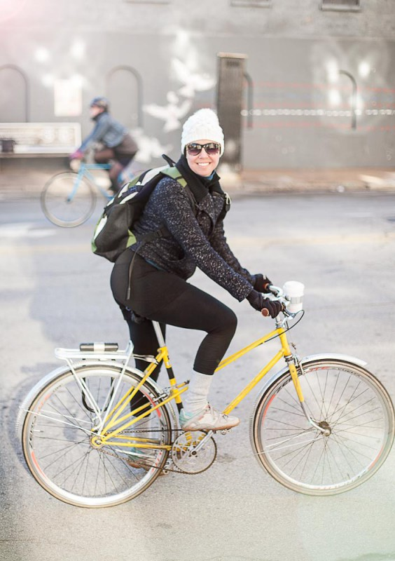 Eine schöne Frau namens Laura fährt ein gelbes Rad in Chicago und trägt dabei eine weiße Mütze und Sonnenbrille