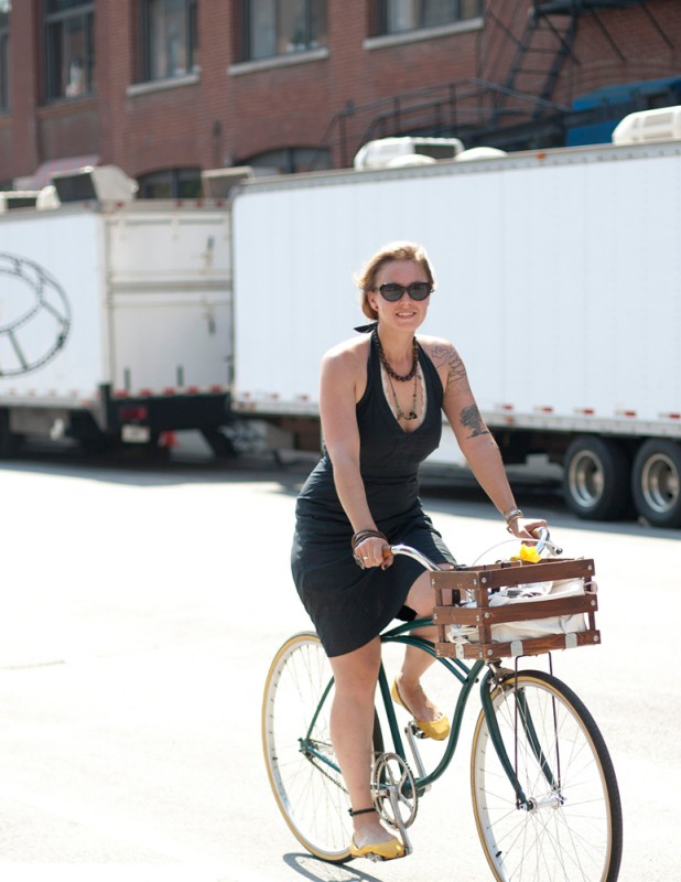 Eine schöne Frau namens Lauren fährt einen Cruiser in Chicago und trägt dabei ein schwarzes Minikleid und Sonnenbrille